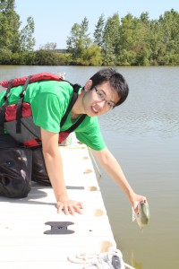 Photo of Jianxun Wang putting robotic fish in a river